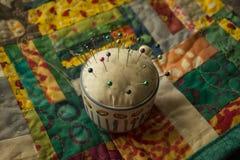 Tekopp Pin Cushion på det färgrika täcket Royaltyfri Bild