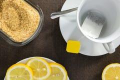Tekopp, skivor av citronen och farin Royaltyfri Foto