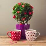 Tekoppar och trädväxt med hjärtaformer för valentin dagberöm Royaltyfri Bild