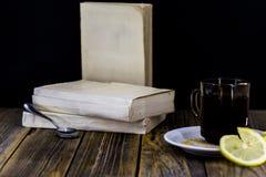 Tekoppen med citronen, träbakgrund, bokar arkivbild
