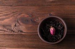 Tekoppen, med lösa torkade svarta teblad och en rosa knopp för te, är på trätabellen royaltyfri foto