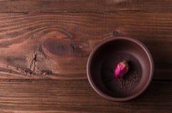 Tekoppen och den rosa knoppen för te är på trätabellen arkivbilder