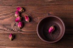 Tekoppen och något te steg knoppar är på trätabellen arkivfoto