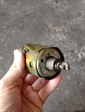 Tekort uitgeput die solenoïdedeel van de oude motor van de benzinestartmotor wordt gedemonteerd stock foto