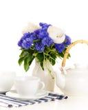 Tekruka och koppar på tabellen med den blåa och vita buketten på vit b Royaltyfri Foto