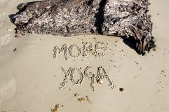 Tekst «Więcej joga «pisać w piasku na słonecznym dniu zdjęcia royalty free