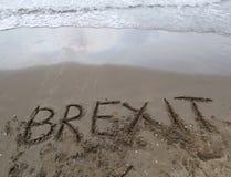 Tekst BREXIT op het zand van het overzeese wachten dat door w moet worden gewist royalty-vrije stock foto