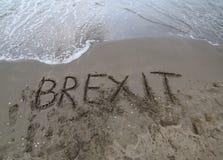 Tekst BREXIT op het zand van het overzeese wachten dat door w moet worden gewist royalty-vrije stock afbeelding