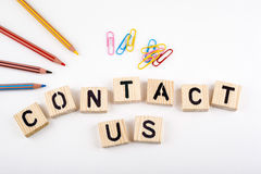 Tekst: Contacteer ons van houten letterson op wit bureau Stock Afbeeldingen