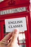 Tekst Engelse klassen in een uithangbord en een rode telefooncel royalty-vrije stock afbeeldingen