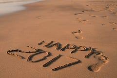 Tekst gelukkige 2017 in het zand van een strand Stock Afbeelding