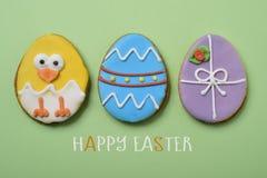 Tekst gelukkige Pasen, kuiken en verfraaide eieren stock afbeelding