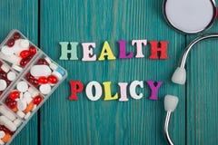 Tekst & x22; Gezondheid policy& x22; van gekleurde houten brieven, stethoscoop en pillen stock fotografie