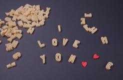 Tekst I houdt van u geschreven met macaroni in de vorm van brieven op zwarte houten lijstachtergrond stock fotografie