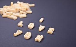 Tekst I houdt van u geschreven met macaroni in de vorm van brieven op zwarte houten lijstachtergrond stock foto's