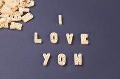 Tekst I houdt van u geschreven met macaroni in de vorm van brieven op zwarte houten lijstachtergrond stock afbeeldingen