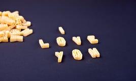 Tekst I houdt van u geschreven met macaroni in de vorm van brieven op zwarte houten lijstachtergrond royalty-vrije stock afbeelding