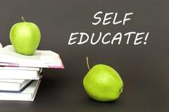 Tekst jaźń kształci, dwa zielonego jabłka, otwarte książki z pojęciem zdjęcia royalty free