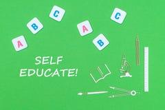 Tekst jaźń kształci, od above drewnianych minitures szkolnych dostaw i abc listów na zielonym tle fotografia stock