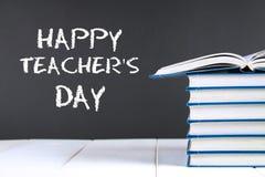 Tekst kreda na chalkboard: Szczęśliwy nauczyciela dzień Szkolne dostawy, biuro, książki, jabłko fotografia stock