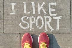 Tekst lubię sport piszę na szarym bruku z kobiet nogami w sneakers, widok z góry obrazy royalty free