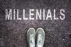 Tekst Millennials op asfalt met schoenen wordt geschreven die royalty-vrije stock fotografie