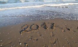 Tekst 2017 op het strand en de golven Stock Afbeeldingen