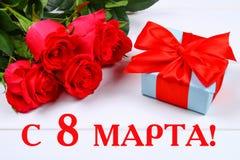 Tekst in Rus: 8 maart Internationale Vrouwen` s Dag Rozen en een gift op een witte achtergrond stock foto's