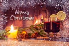 Tekst Vrolijke Kerstmis op de achtergrond van een mooi beeld met overwogen wijn en een open haard Romantische Kerstkaart stock afbeeldingen