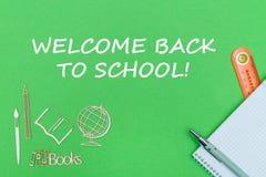 Teksta powitanie z powrotem szkoła, szkolnych dostaw drewniane miniatury, notatnik na zielonym tle Fotografia Royalty Free