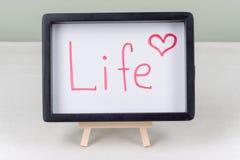 Teksta słowa życie, czerni rama na bielu stole, obraz stock