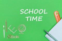 Teksta szkolny czas, szkolnych dostaw drewniane miniatury, notatnik na zielonym tle Obrazy Royalty Free