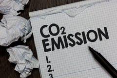 Teksta szyldowy pokazuje emisja co2 Konceptualny fotografii laszowanie szklarniani gazy w atmosfera markiera nad notatnikiem prze zdjęcie stock