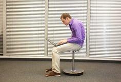 Teksthals - mens in het slouching van positie die met computer werken stock foto's