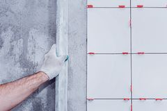 tekstur ceramiczne ceranic płytki Mistrz kłaść ceramiczne płytki na ścianie i rysuje one za używać dodatku specjalnego poziom zdjęcie stock