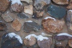 Tekstura jest szara z czerwoną kamienną ścianą z wielkimi kamieniami, zakrywającymi z śniegiem obrazy stock