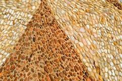 Tekstura kamienna ściana droga od małych round i owalu kamieni z abstrakcjonistycznymi trójgraniastymi wzorami deseniował trójbok zdjęcie stock