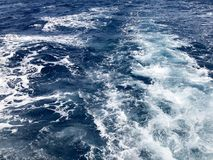 Tekstura kipi błękitna denna słona woda z fala, rozlewa, bąble, piana, ślada po tym jak szybka spławowa fura, łódź znowu zdjęcia stock