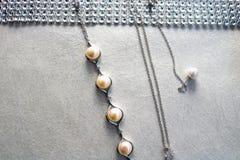 Tekstura z perełkową biżuterią, perły, srebro łańcuchy, kryształy cenni kamienie, diamenty, diamenty na świetle - szary tło zdjęcia stock