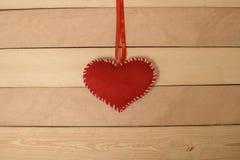 Tekstylny czerwony serce na taśmie na drewnianej teksturze Obrazy Royalty Free