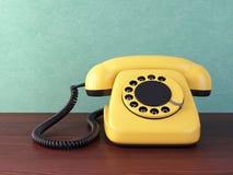 Teléfono amarillo en la tabla de madera Imagen de archivo libre de regalías
