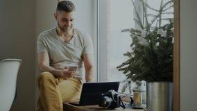 Teléfono atractivo del smartphone de la ojeada del hombre joven que se sienta en alféizar con el ordenador portátil y cámara en c fotografía de archivo