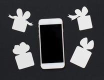 Teléfono blanco con las cajas de regalo en fondo negro La plantilla blanco y negro de la bandera con el corte del smartphone y de Fotos de archivo