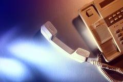 Teléfono blanco del escritorio de oficina con el microteléfono en asimiento Imagenes de archivo