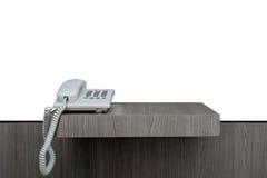Teléfono blanco en el fondo de madera del blanco de la tabla Imágenes de archivo libres de regalías