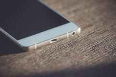 Teléfono blanco en una tabla de madera Imagenes de archivo