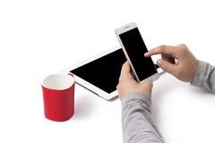 Teléfono blanco verticalmente sostenido en manos del ` s del hombre Una taza roja y un Ipad en la tabla blanca Foto de archivo