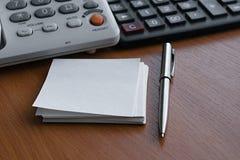 Teléfono, calculadora, Libro Blanco para las notas y bolígrafo del metal que miente en una tabla de madera ligera en la oficina e Fotos de archivo libres de regalías