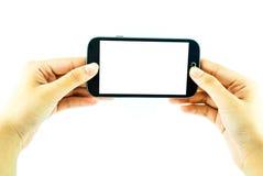 Teléfono celular con la pantalla táctil en mano femenina en el fondo blanco imagen de archivo