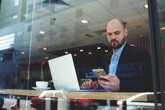 Teléfono celular confiado joven del uso del hombre de negocios durante rotura de trabajo del café fotografía de archivo libre de regalías